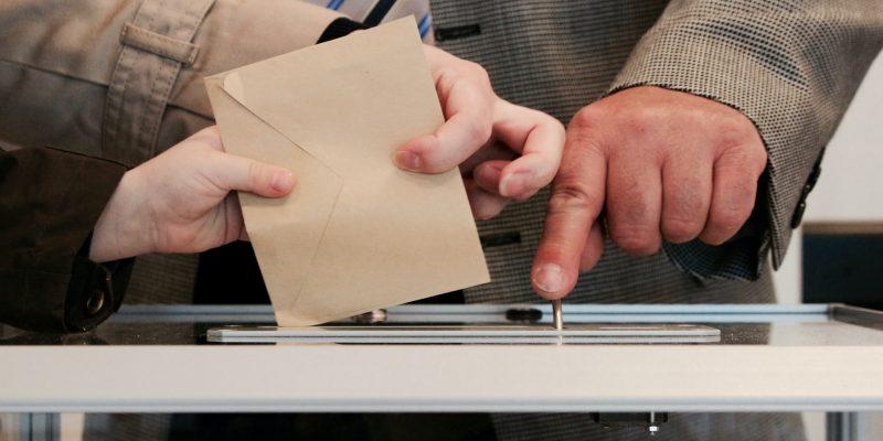 Ein Wahlumschlag wird in die Wahlurne eingeworfen, ein Wahlhelfer ist anwesend